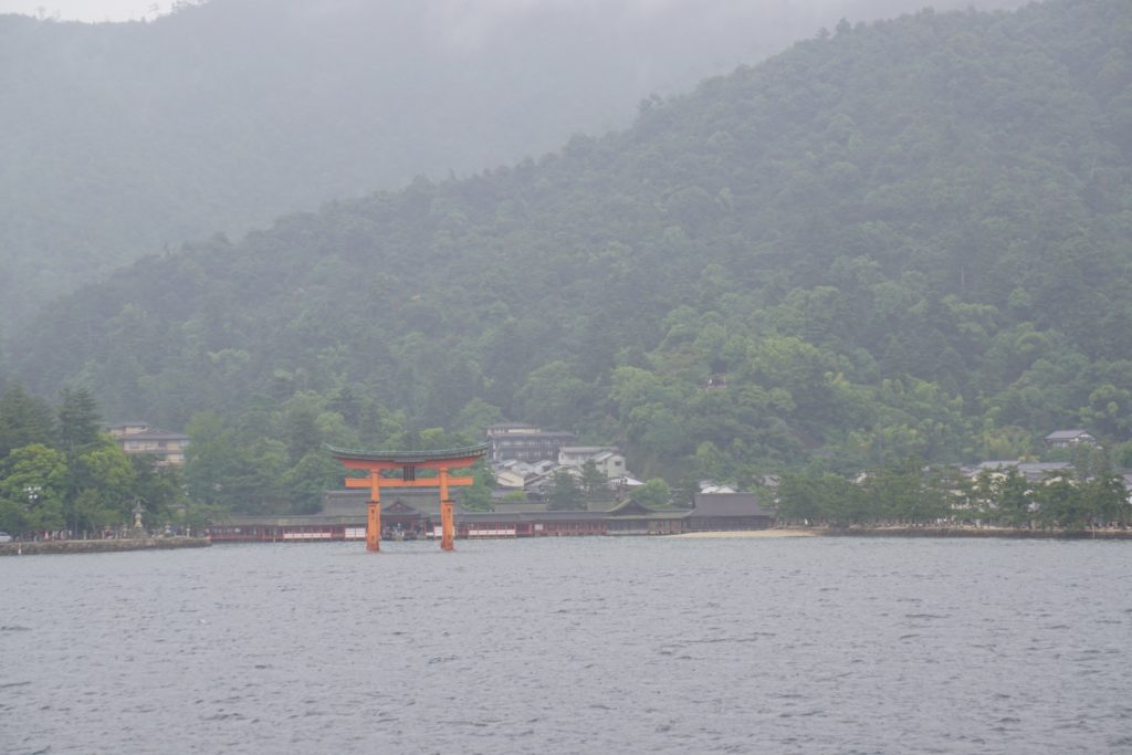 Foggy view of a mountain a orange torii gate, Itsukushima Shrine on Miyajima Island, Japan is in the foreground.