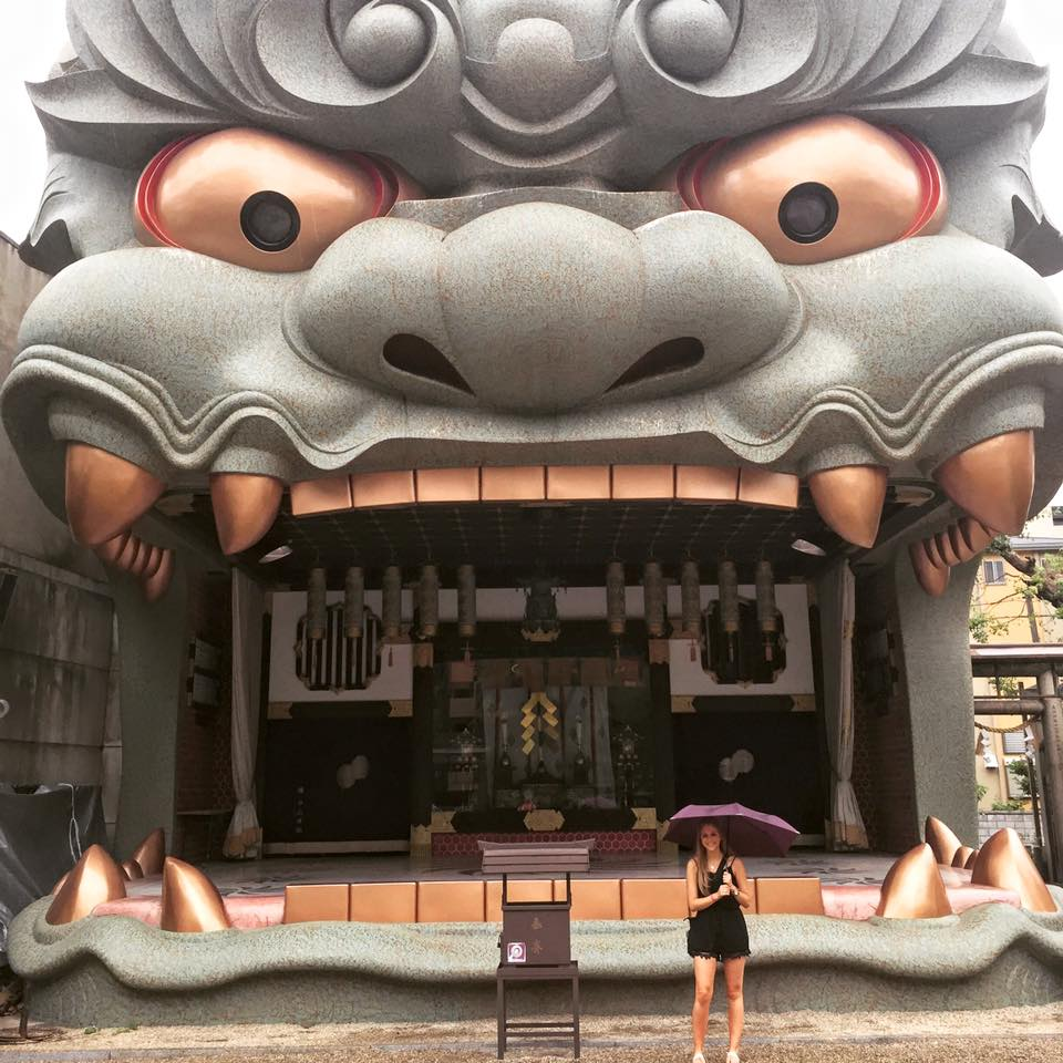 Woman holding an umbrella standing in front of a large shrine that resembles a dragon's face (Namba Yasaka Shrine - Osaka, Japan)