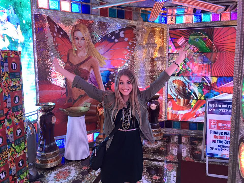 Girl standing in front of a colorful display with arms open.