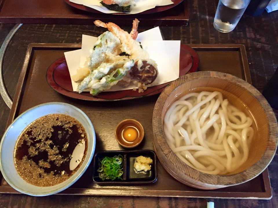 A bowl of broth, udon noodles, and assorted tempura.