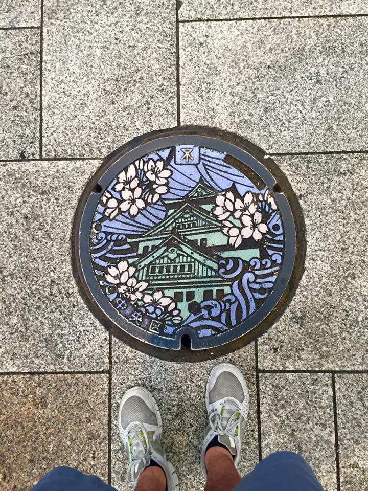 A manhole cover that has the design of Osaka Castle in Osaka, Japan