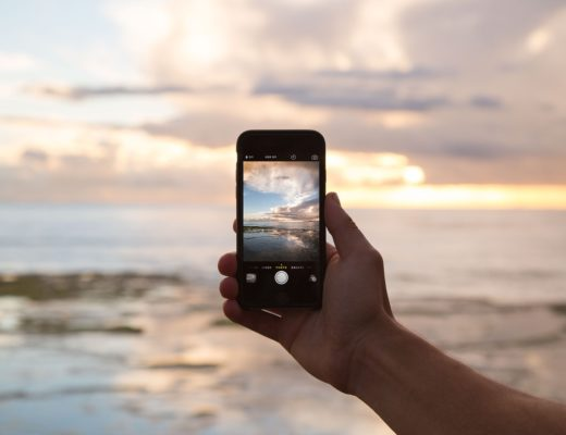 Taking a photo of a beach sunset on a cell phone.