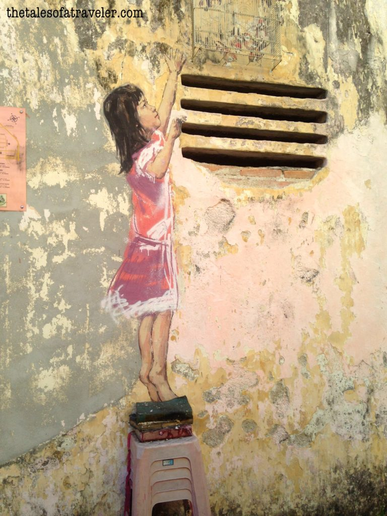 """""""Girl with stool and birdcage"""" by Ernest Zacharevic - coolest street art in Malaysia"""