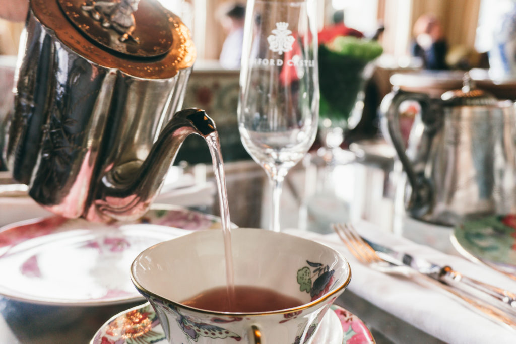 A silver tea pot pouring tea into a tea cup at Ashford Castle afternoon tea