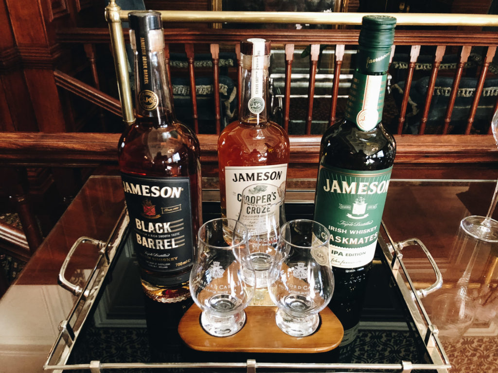 Three types of Irish whisky on a bar cart.