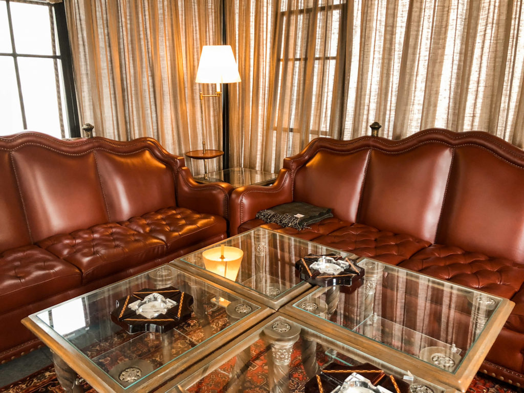 Leather couches by a glass coffee table.