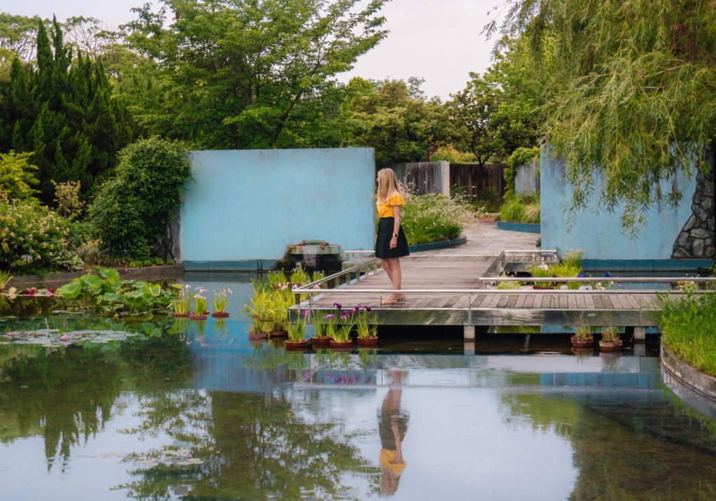 Girl standing on a dock looking out at the water of a pond at Uminonakamichi Seaside Park in Fukuoka