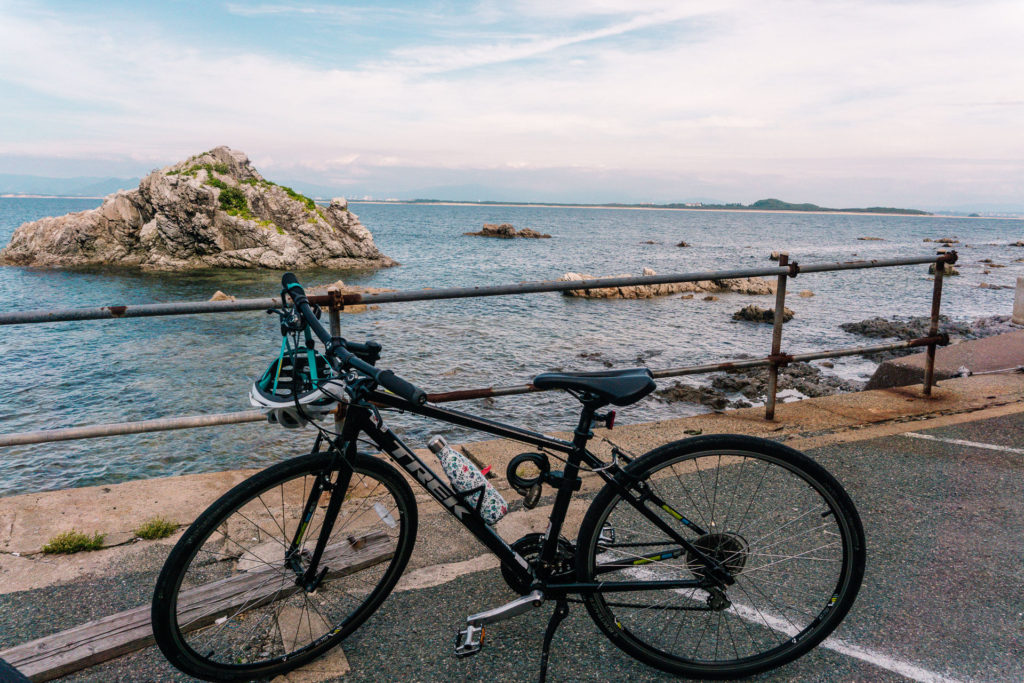 Parked bicycle with a view of the ocean behind it.