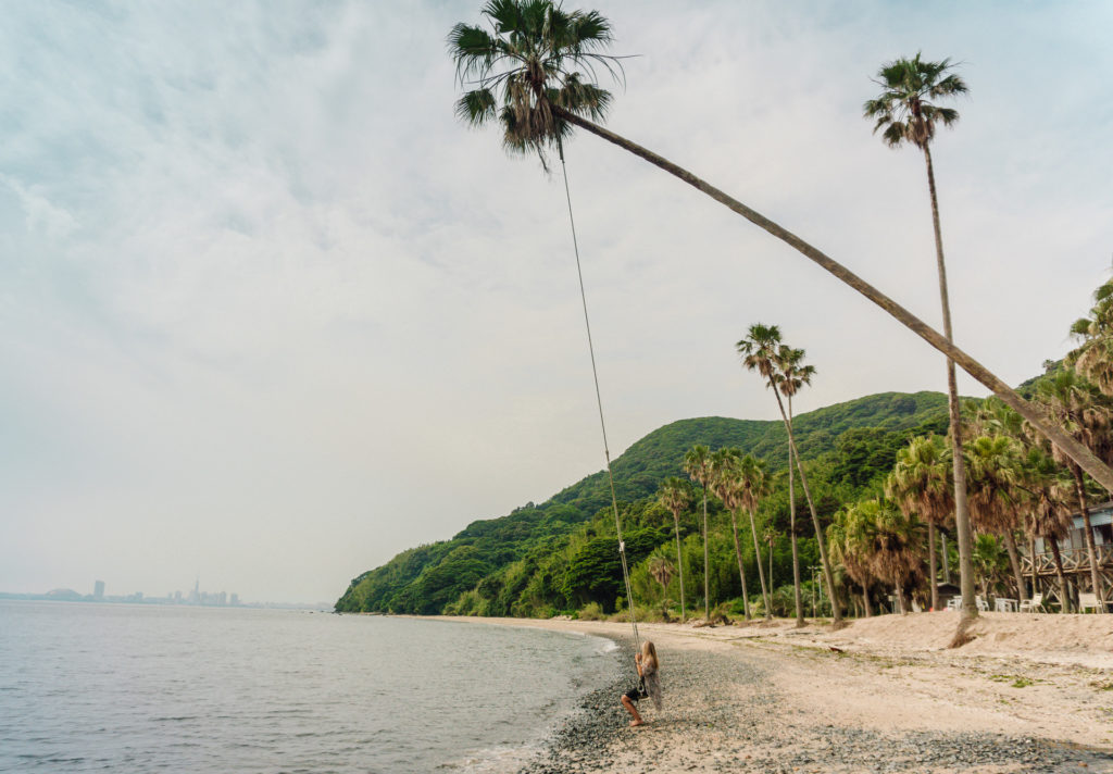 Woman swinging on a swing tied to a palm tree at Nokonoshima Island - Fukuoka