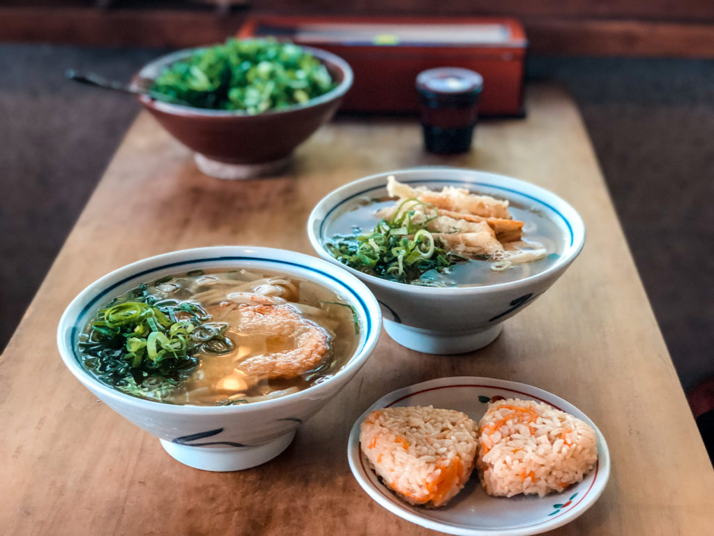 Two bowls of udon noodles and two onigiri (rice balls)