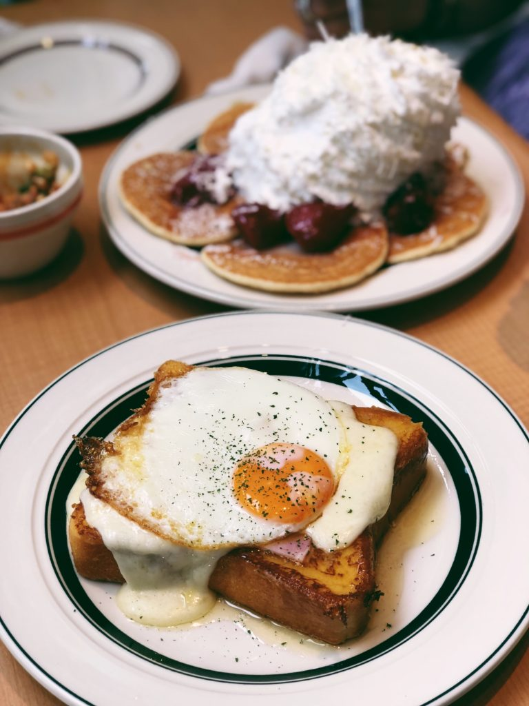 A plate of toast with ham, cheese, and a fried egg on top.