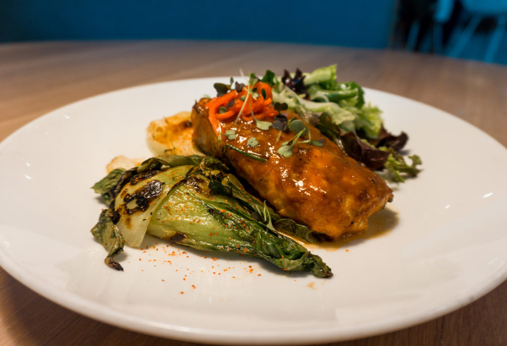 Miso glazed salmon with a side of greens from The Drake restaurant in OKC