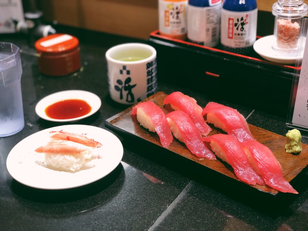 A plate of sashimi (sushi) with two pieces of king crab and six pieces of fatty tuna