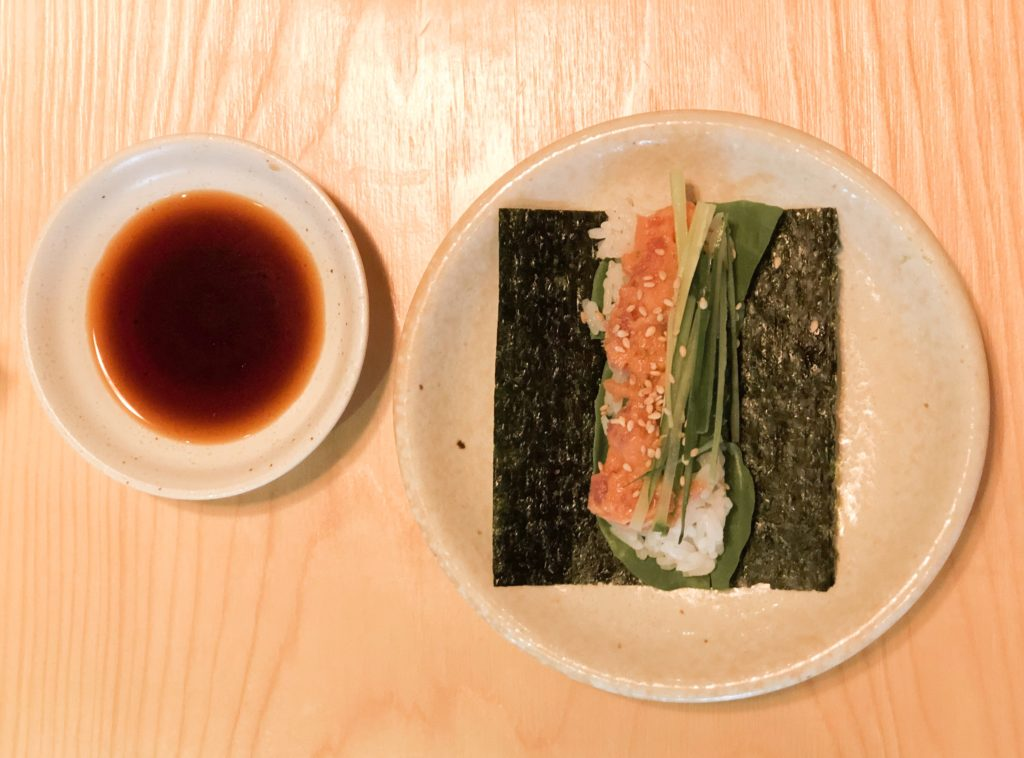 Bowl of soy sauce and a plate with a salmon sushi hand roll from Ganpachi Nori-Tamaki in Tokyo, Japan