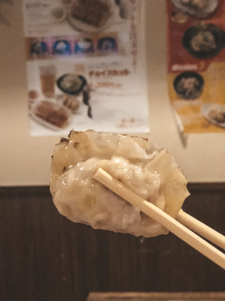 Chopsticks holding a pan-fried gyoza from Chao Chao Gyoza in Kyoto, Japan