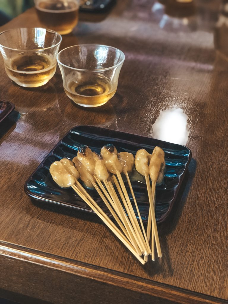 Sticks of aburi mochi (Japanese sweet rice cake) on a plate from Ichiwa in Kyoto, Japan