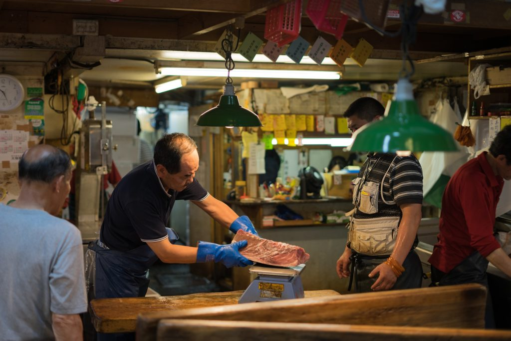 Man holding a large piece of tuna at an auction at Tsukiji Fish Market in Tokyo