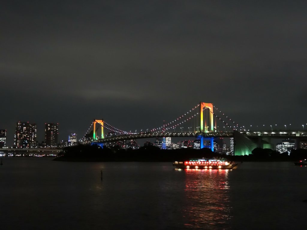 A bridge at night with rainbow lights on it (Rainbow Bridge Odaiba in Tokyo)