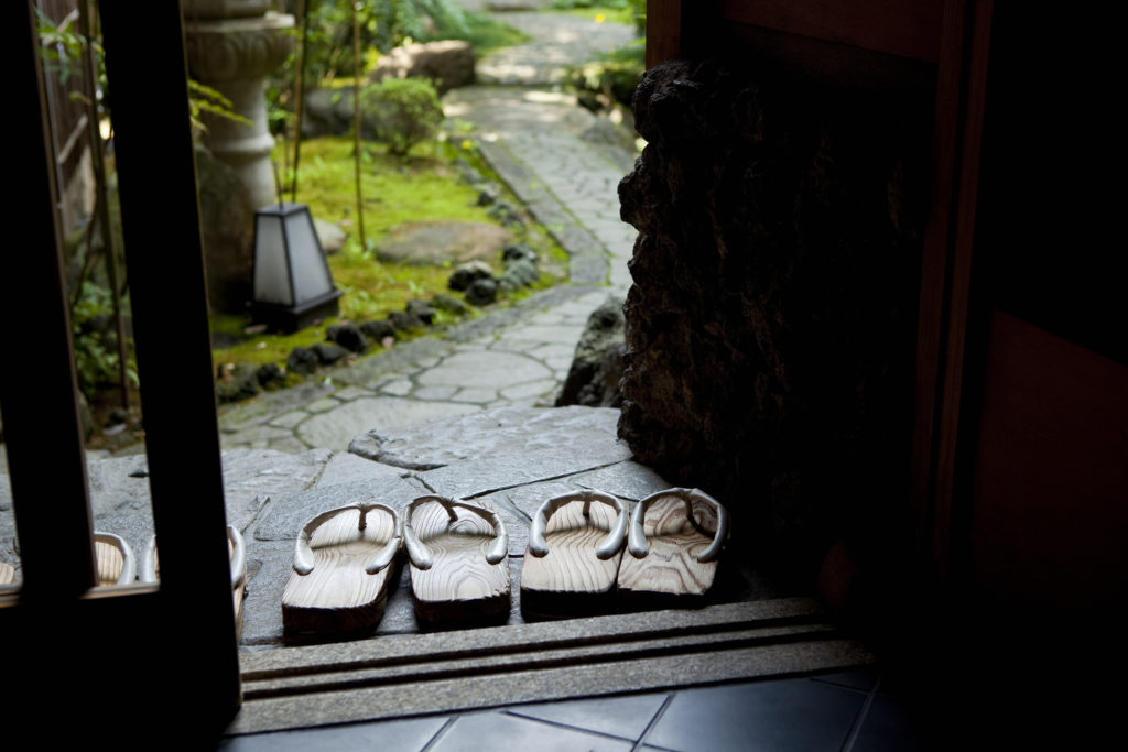 Two sets of Japanese sandals outside the door of a Japanese garden.