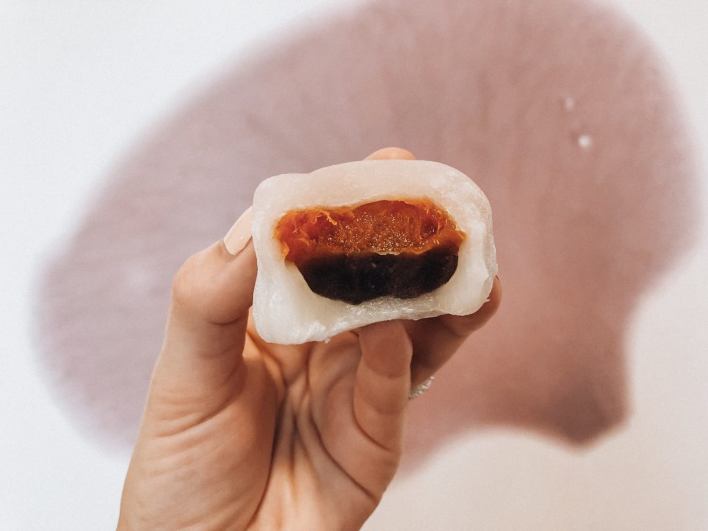 Hand holding a Japanese sweet called daifuku (a sweet rice flour dumpling filled with a layer of red bean paste and a dried apricot on top.