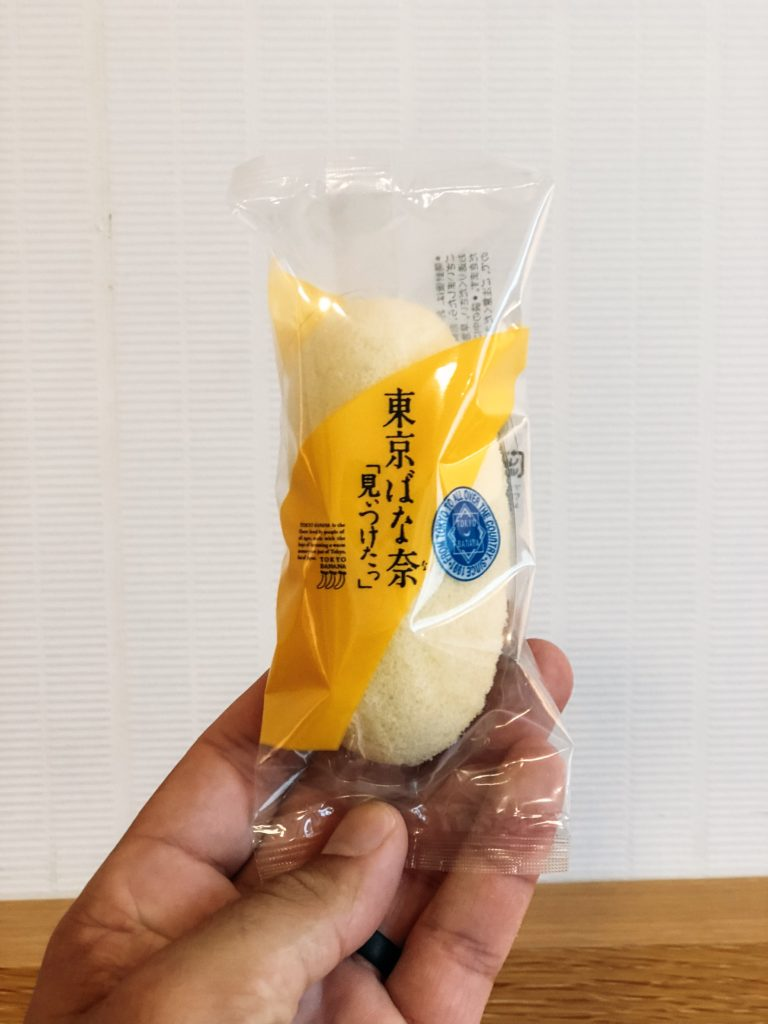 Hand holding a packaged light yellow banana shaped cake dessert (Tokyo banana)