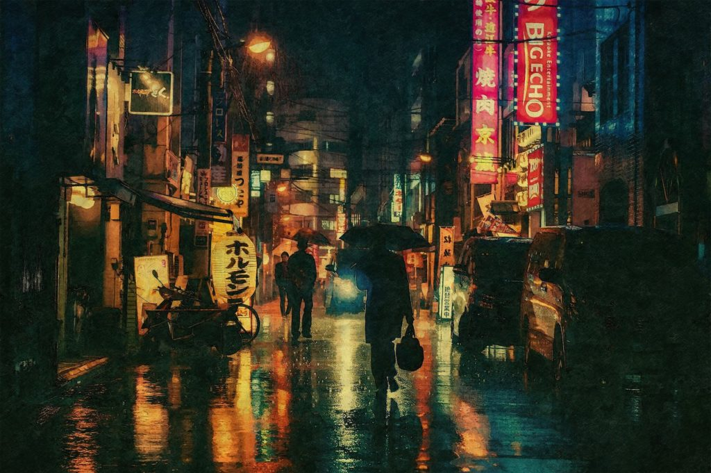 A street in Japan at night with glowing signs. It is raining and the people walking on the street are carrying umbrellas.