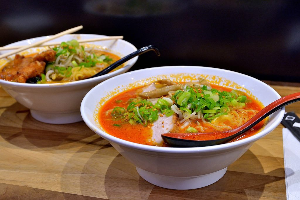 Two white bowls containing ramen noodles in a red broth topped with green onion.
