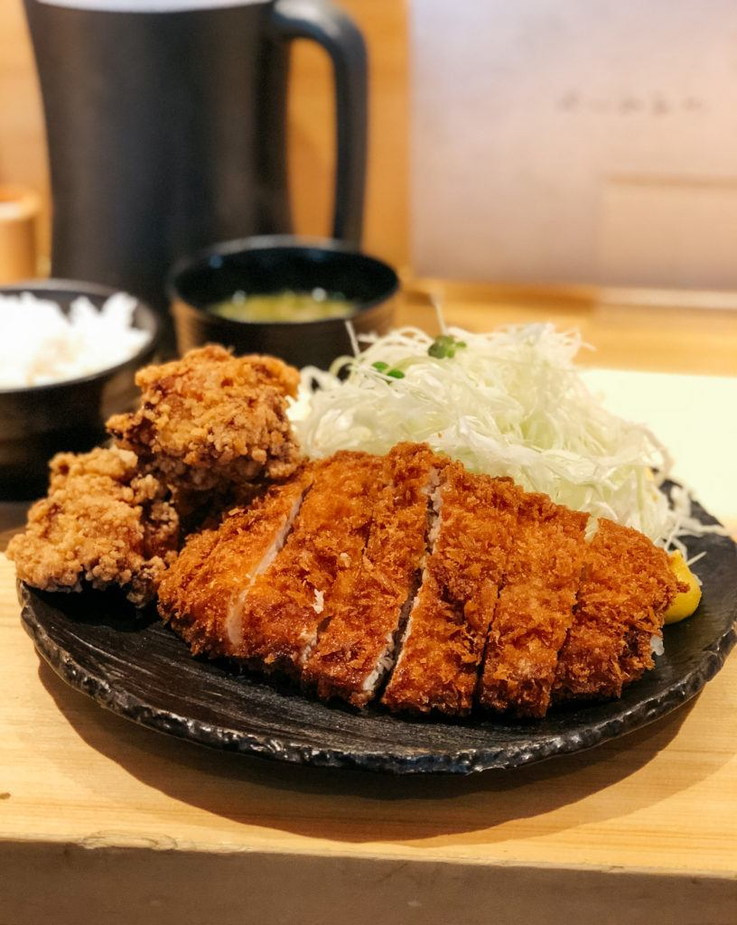Tonkatsu, fried pork cutlet with karaage, fried chicken and a side of cabbage.